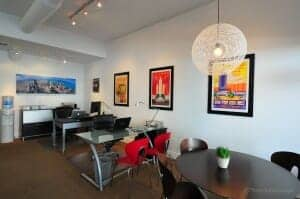 Interior photo of modern style Chicago West Loop real estate office with white walls, high exposed white concrete ceilings, three brightly colored Chicago world's fair posters on the wall modern chandelier hanging over round walnut contemporary meeting table - a warm and inviting office environment for clients and real estate agents.