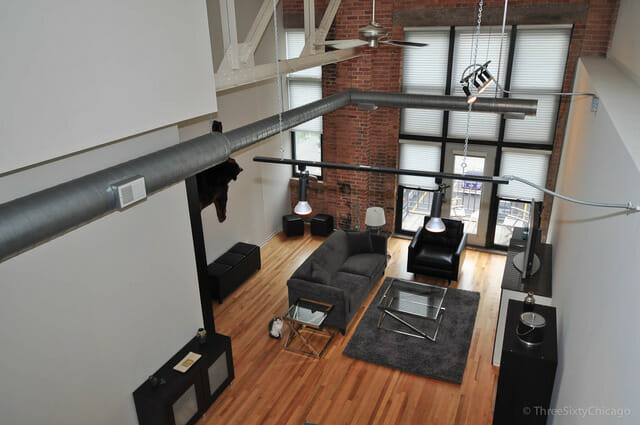 Photo of two story West Loop loft interior living space in Beacon Lofts - huge wall of windows at the end, black and grey modern furniture against white walls and exposed brick.