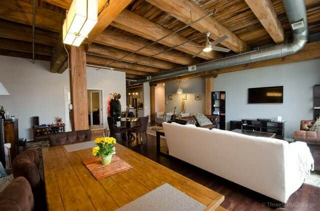 Photo of a loft condo with massive timber beams, exposed ductwork, a white couch and long wooden dining table with interesting rectangular light fixture.