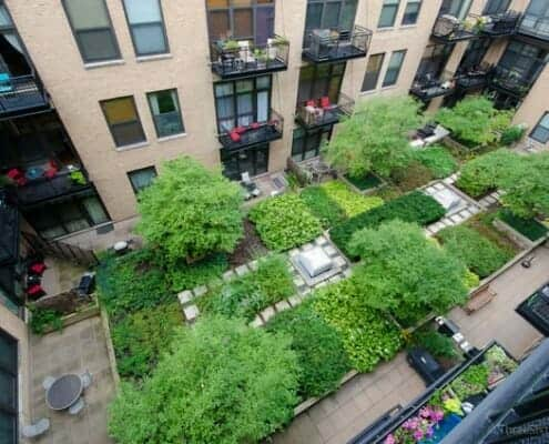 Photo looking down into the lush green interior garden courtyard at No. Ten Lofts in the Chicago West Loop neighborhood. You can see yellow brick building.