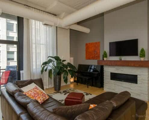 Printers Row Two Bedroom Loft Rental - Chicago loft living space with high concrete ceilings, floor-to-ceiling windows, modern gas fireplace with rustic wood mantle and flat screen tv. Walls are green and beige earth tones.