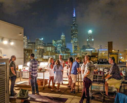 Night Roof Deck photo of a party with Chicago skyline in the back. 933 W. Van Buren, Chicago, IL 60607