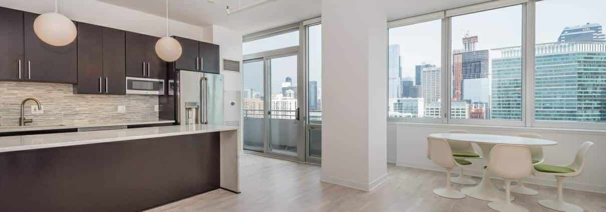 Modern kitchen opens to living and dining area overlooking Chicago skyline.